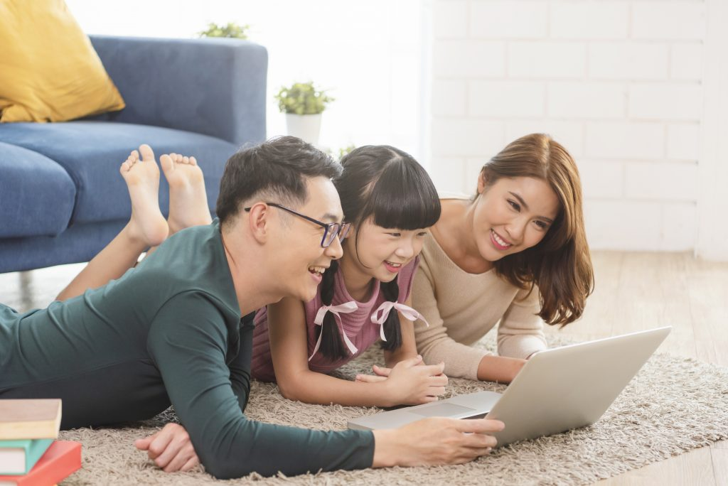 Happy Asian family using computer laptop together on sofa at hom